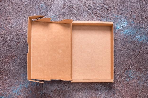Boîte en carton brun simple ouverte, avec couvercle sur fond sombre