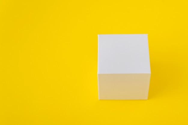 Boîte en carton carré blanc sur jaune