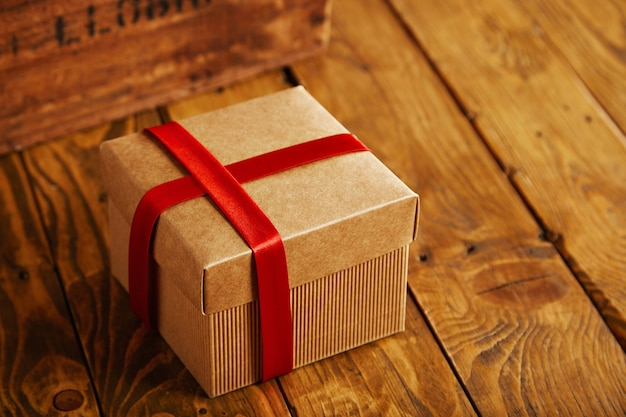 Boîte en carton carré ciblé fermé et emballé avec du ruban de soie rouge sur une table en bois rustique à côté de caisse vintage