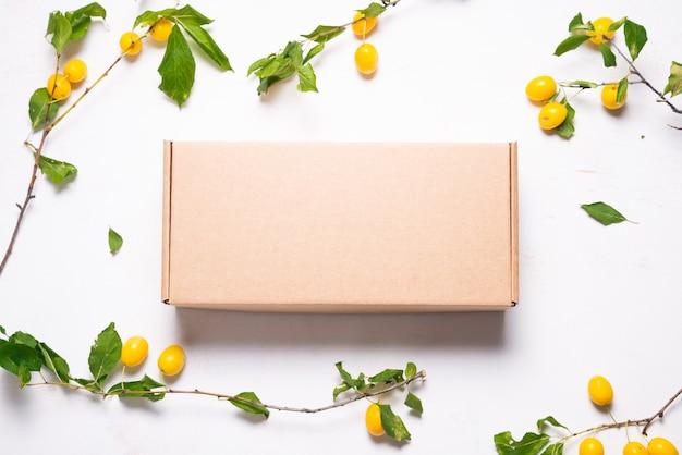 Boîte en carton en carton brun avec des feuilles vertes fraîches