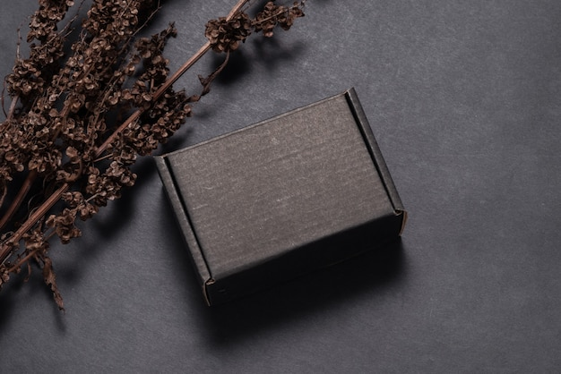 Boîte en carton en carton noir décorée d'une maquette de branche séchée