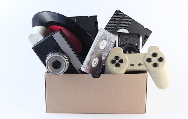 Boîte en carton avec cassettes vidéo, appareil photo rétro, disque vinyle, cassette audio, manette de jeu sur fond blanc.