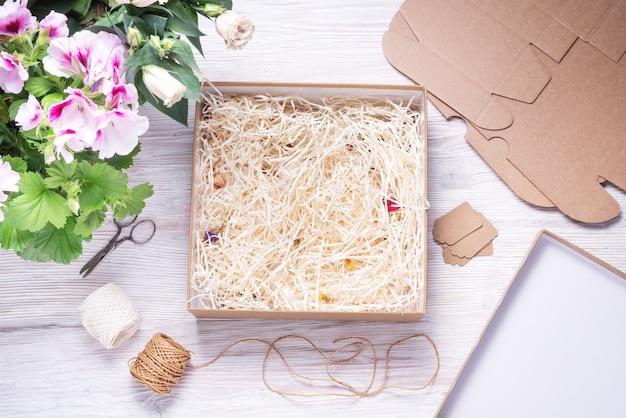 Boîte en carton cbrown avec remplissage de papier sur fond de bois