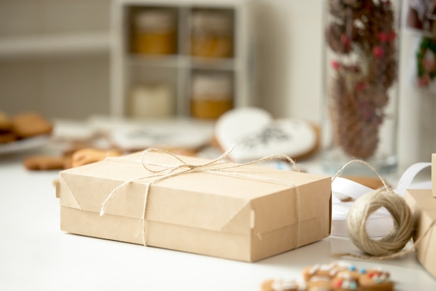 Boîte en carton, colis postal enveloppé en papier kraft brun attaché