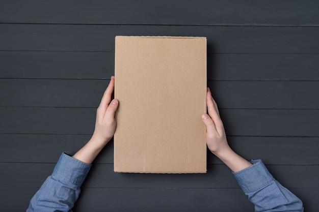 Boîte en carton dans les mains des enfants sur fond noir.