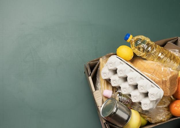 Boîte en carton avec divers produits, fruits, pâtes, huile de tournesol dans une bouteille en plastique et conservation. concept de don, vue de dessus