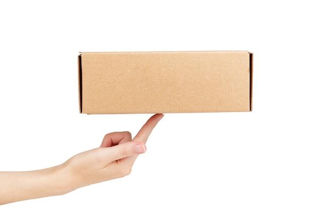 Boîte en carton sur doigt féminin. livraison express à domicile rapide. style de maquette et place pour le texte. concept d'expédition de colis et de nourriture. isolé sur fond blanc.