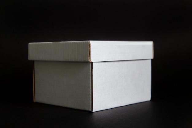 Boîte en carton sur un espace noir. disposition pour la conception de l'image de marque
