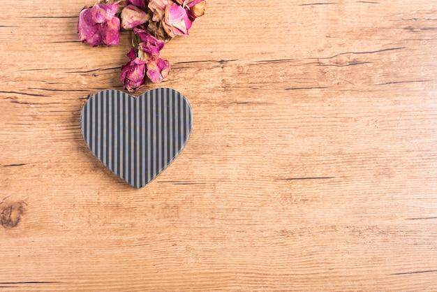 Boîte en carton en forme de coeur de lignes grises et noires sur bois