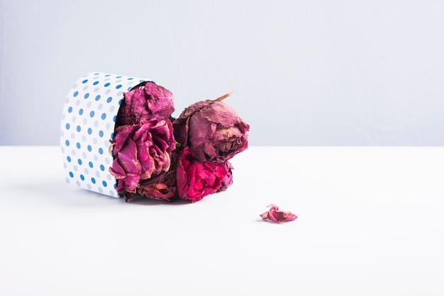 Boîte en carton en forme de cœur à pois bleus, allongée et avec des roses aux pétales séchés