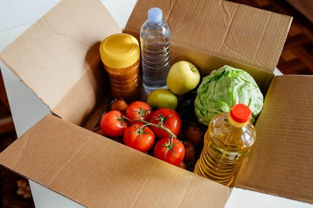 Boîte en carton gros plan avec différents produits alimentaires frais emballés concept de livraison sûre nourriture sociale ne ...