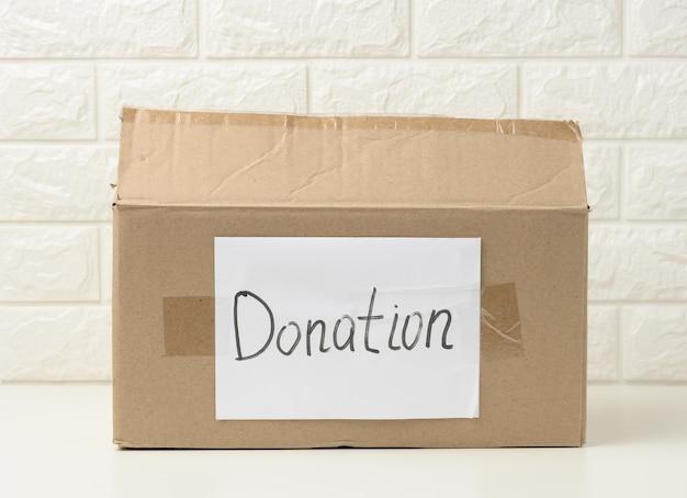 Boîte en carton marron avec une feuille blanche collée et le don d'inscription sur fond blanc, concept d'aide