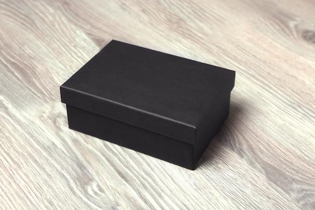 Boîte en carton noir sur table en bois