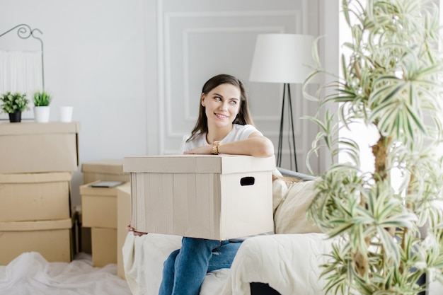 Boîte en carton avec objets personnels entre les mains d'une jeune femme