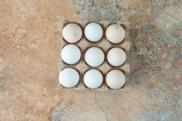 Boîte en carton avec des oeufs blancs frais de poulet sur table en marbre.