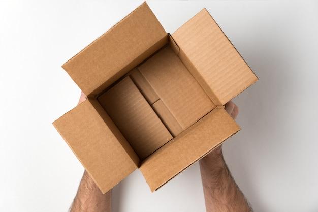 Boîte en carton ouverte vide dans les mains des hommes. concept de prestation de services. .
