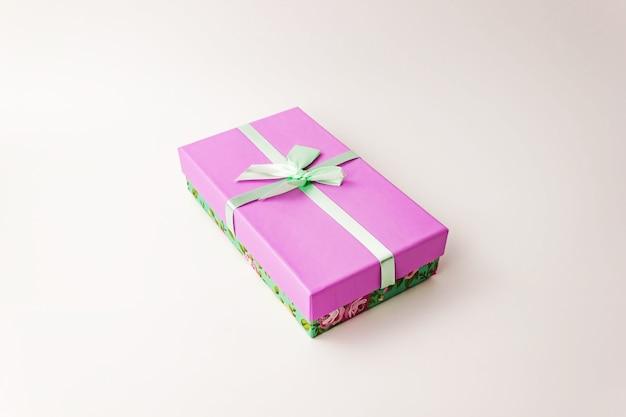 Boîte en carton de papier à couvercle violet à fleurs unique avec couvercle vert et arc sur blanc. concept actuel de vacances. vue rapprochée. flou sélectif. espace de copie de texte.