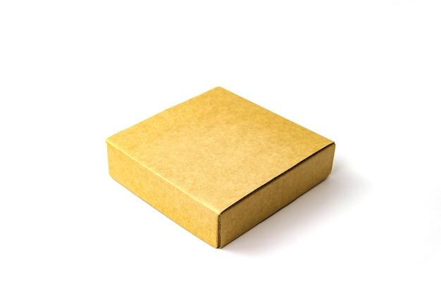 Boîte en carton de papier kraft plat couleur marron unique isoler sur blanc. vue rapprochée. flou sélectif. espace de copie de texte. emballage, transport, concept de déménagement