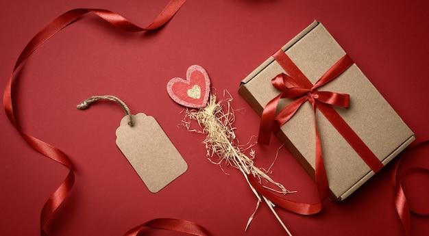 Boîte en carton rectangulaire brun attaché avec un ruban de soie rouge sur une surface rouge, vue du dessus, gros plan