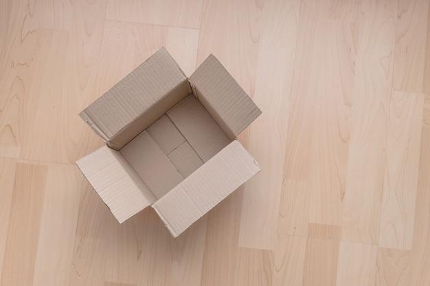 Boîte en carton rectangulaire ouverte vide sur bois