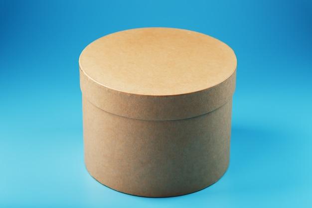Boîte en carton ronde sur fond bleu, espace libre.