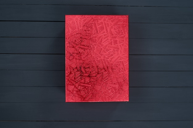 Boîte en carton rouge fermé brillant sur un bois noir