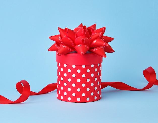 Boîte en carton rouge ronde à pois blancs avec un gros noeud