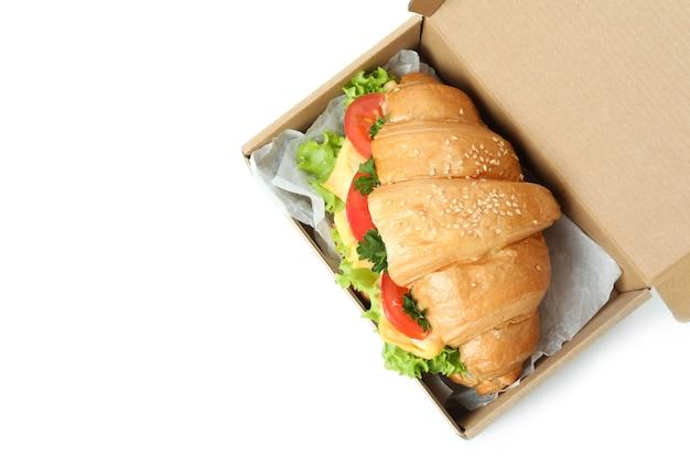 Boîte en carton avec sandwich croissant isolé sur blanc