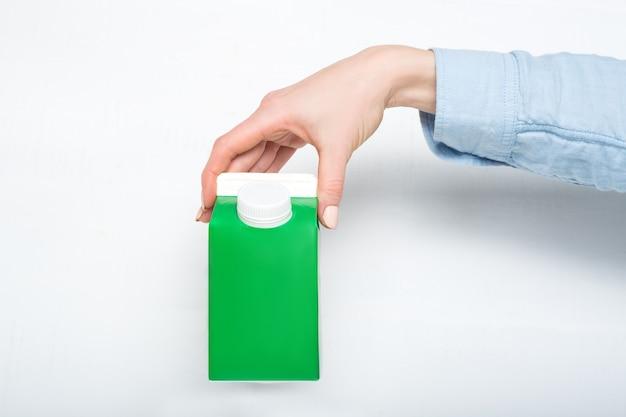 Boîte en carton vert ou emballage de tetra pack avec un capuchon dans une main féminine. fond blanc