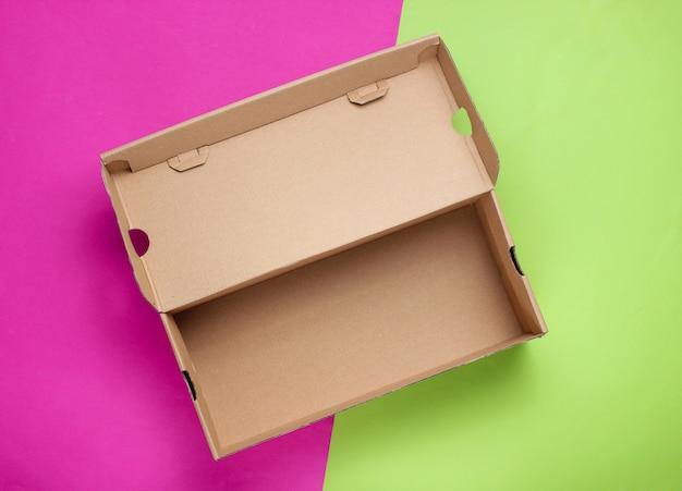 Boîte en carton vide sur une surface colorée.