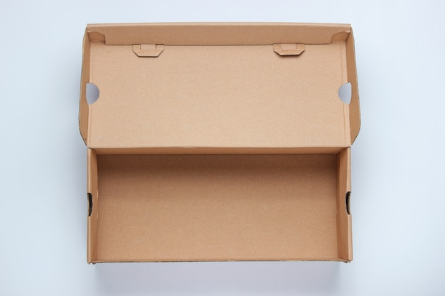 Boîte en carton vide sur une surface grise.