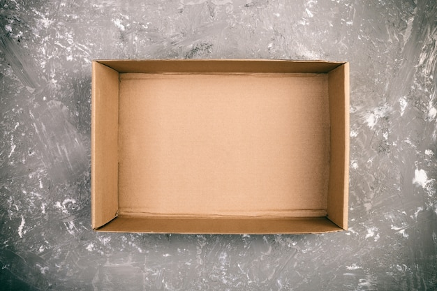 Boîte de carton vierge brune ouverte sur une surface grise