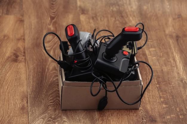 Boîte en carton avec de vieux joysticks filaires et manettes de jeu sur un plancher en bois