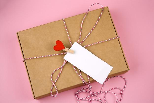 Boîte en carton vue de dessus avec une broche en tissu avec coeur rouge et étiquette blanche vide