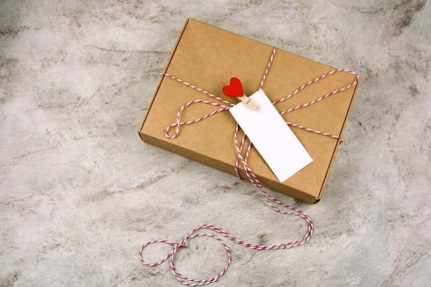 Boîte en carton vue d'op avec épingle en tissu avec coeur rouge et étiquette blanche vide