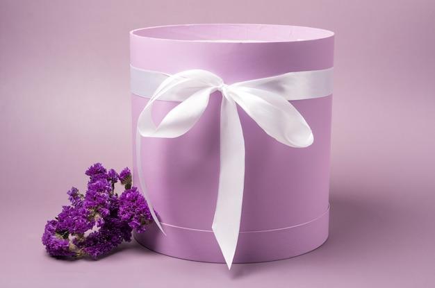 Boîte à chapeau rose clair avec des fleurs violettes sur fond rose clair