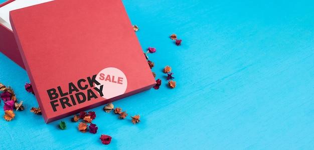 Boîte de chargement rouge sur table en bois bleue. concept de vente vendredi noir