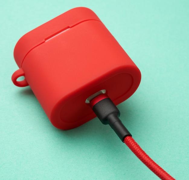 Boîte avec un chargeur de casque dans un étui rouge attaché au câble sur fond vert
