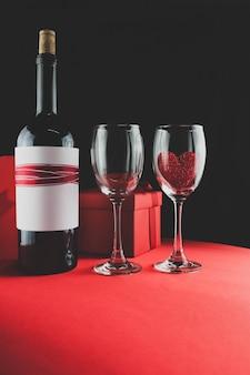 Boîte de chocolats avec une bouteille de vin et deux verres une avec un coeur