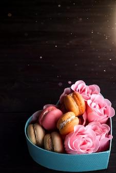 Boîte coeur bleu avec macarons et rose sur fond en bois foncé, espace copie