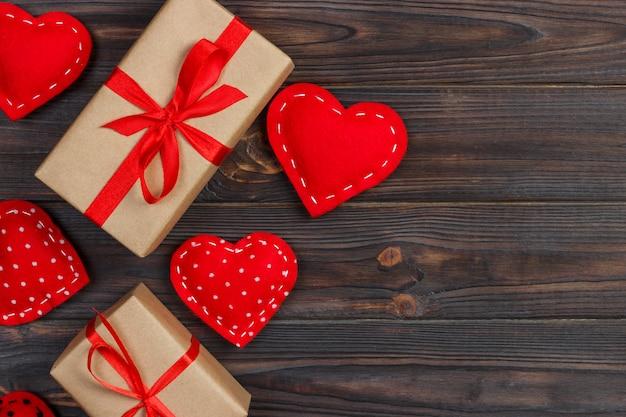 Boîte coeur et cadeau avec ruban rouge sur fond en bois