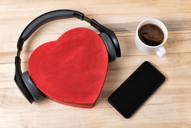 Boîte coeur avec casque, téléphone et tasse de café sur fond en bois. vue de dessus