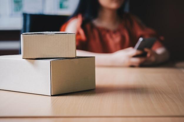 Boîte de colis avec arrière-plan flou contient femme à l'aide de smartphone