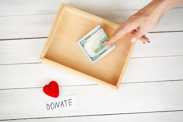 Boîte de collecte de fonds de bienfaisance avec des dollars sur fond de bois blanc