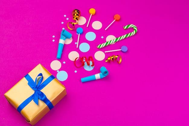 Boîte avec des confettis éclaboussés de ruban, mecs et autres accessoires de fête