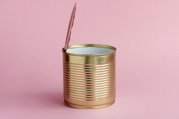 Boîte de conserve en métal vide sur fond rose. concept de tri des déchets et ordures