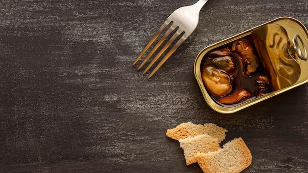 Boîte de conserve de moules à angle élevé avec du pain grillé et une fourchette avec copie-espace