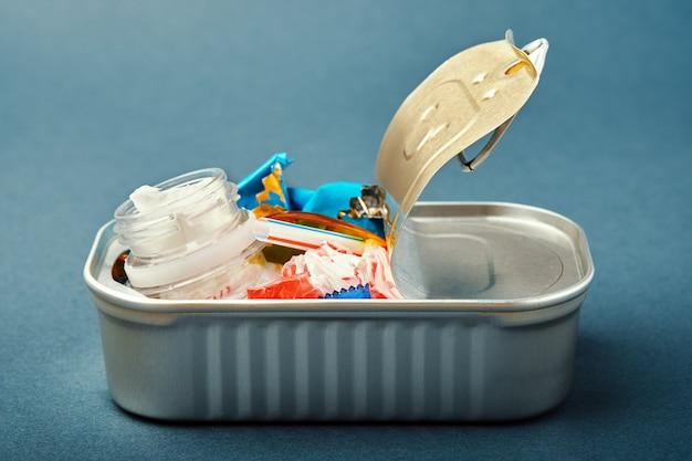 Boîte de conserve ouverte. déchets plastiques au lieu de poissons à l'intérieur. concept de pollution plastique océanique