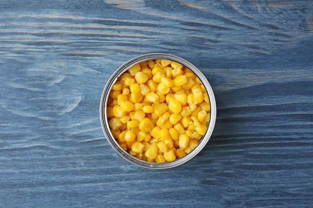 Boîte de conserve ouverte avec grains de maïs sur table en bois
