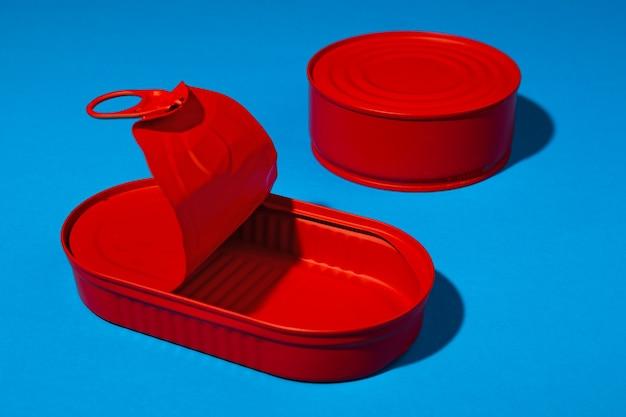 Boîte de conserve rouge sur la surface bleue se bouchent